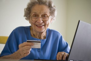 Smiling senior woman using credit card and laptop