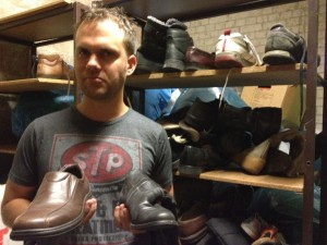 Bjorn holds up some shoes that need their mates during our shoe-sorting service project in Berlin. (Photo by Jammie Karlman)